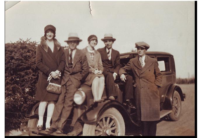 Un grupo de personas con la moda y un coche de la época. (www.goorin.com).